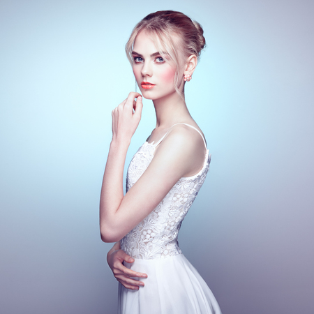 elegance fashion girls look sensuality young: Fashion portrait of beautiful young woman with blond hair. Girl in white dress on white background