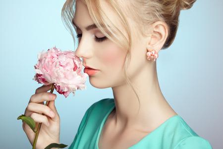 우아한 헤어 스타일을 가진 아름 다운 관능적 인 여자의 초상화입니다. 완벽한 메이크업. 금발 소녀입니다. 패션 사진. 꽃