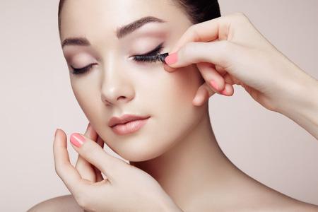 artistas: Artista de maquillaje pegamentos pesta�as. Cara de mujer hermosa. Maquillaje perfecto. Manera de la belleza. Pesta�as. Sombra de ojos cosm�tica Foto de archivo