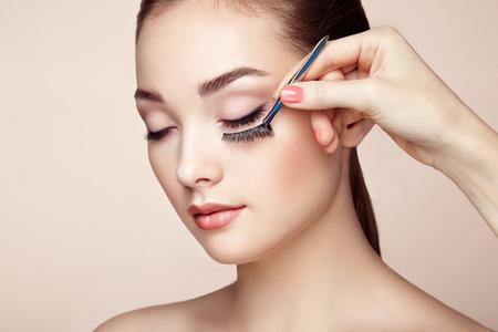 Makeup artist glues eyelashes. Beautiful woman face. Perfect makeup. Beauty fashion. Eyelashes. Cosmetic Eyeshadow