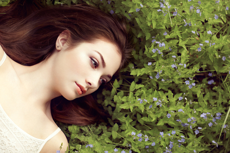 Portrait of a beautiful young woman in summer garden. Girl on nature. Spring flowers. Fashion beauty Stock Photo