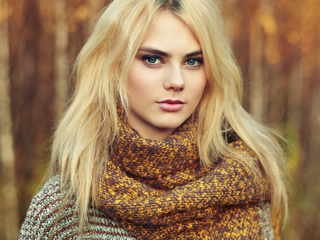 greatcoat: Portrait of young beautiful woman in autumn pullover. Fashion photo. Blonde girl. Perfect make-up Stock Photo