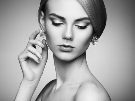 mode: Porträtt av vacker sensuell kvinna med elegant frisyr. Perfekt makeup. Blond tjej. Mode foto. Smycke. Svart och vitt