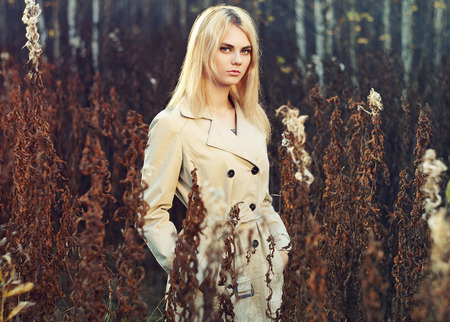 topcoat: Portrait of young beautiful woman in autumn cloak. Fashion photo. Blonde girl. Perfect make-up Stock Photo