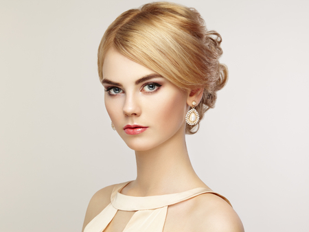 hairstyles: Portrait of beautiful sensual woman with elegant hairstyle.  Perfect makeup. Blonde girl. Fashion photo. Jewelry and dress