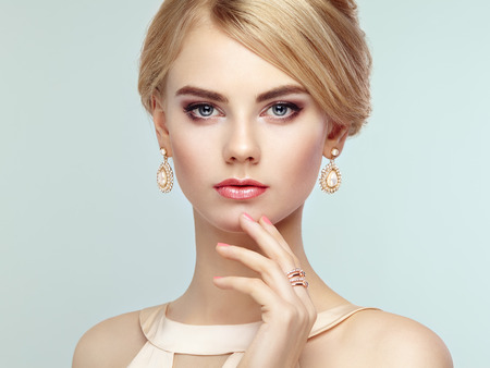 white dresses: Portrait of beautiful sensual woman with elegant hairstyle.  Perfect makeup. Blonde girl. Fashion photo. Jewelry and dress