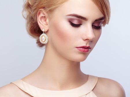 Portret van mooie sensuele vrouw met elegante kapsel. Perfecte make-up. Blond meisje. Fashion foto. Sieraden en jurk