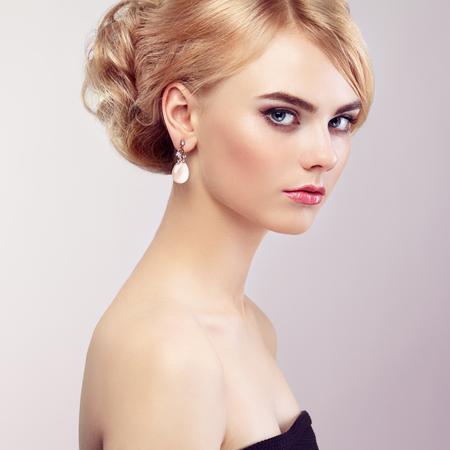 mujeres fashion: Retrato de la hermosa mujer sensual con elegante estilo de peinado. Maquillaje perfecto. Chica rubia. Foto de moda. Joyería y vestido