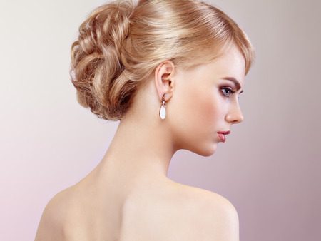wedding hairstyle: Portrait of beautiful sensual woman with elegant hairstyle.  Perfect makeup. Blonde girl. Fashion photo. Jewelry and dress