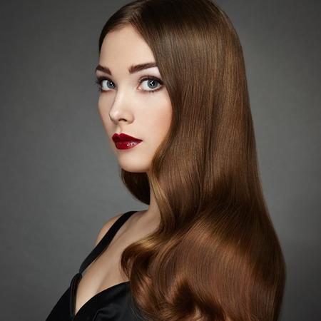 mujeres elegantes: Retrato de moda de mujer elegante con el pelo magnífico. Niña morena. Maquillaje perfecto. Chica en vestido negro. El pelo rizado