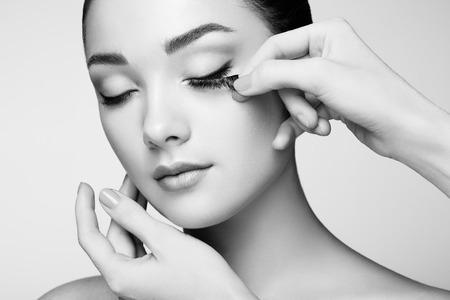 visagist: Makeup artist glues eyelashes. Beautiful woman face. Perfect makeup. Beauty fashion. Eyelashes. Cosmetic Eyeshadow