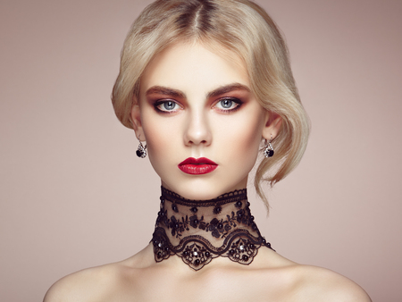 ladylike: Portrait of beautiful sensual woman with elegant hairstyle.  Perfect makeup. Blonde girl. Fashion photo. Jewelry and lace Stock Photo