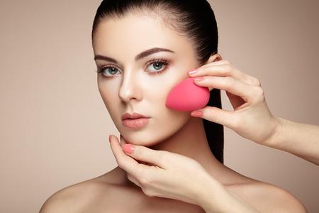 nude woman sexy: Makeup artist applies skintone. Beautiful woman face. Perfect makeup. Skincare foundation. Sponge makeup artist Stock Photo