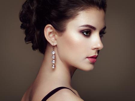 aretes: Retrato de la mujer hermosa joven con la joyería. Chica morena. Maquillaje perfecto. Mujer del estilo de la belleza con los accesorios del diamante