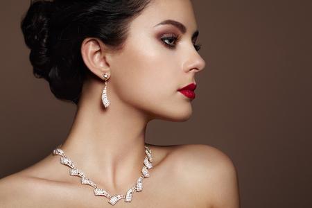 labios sensuales: Retrato de la mujer hermosa joven con la joyería. Chica morena. Maquillaje perfecto. Mujer del estilo de la belleza con los accesorios del diamante