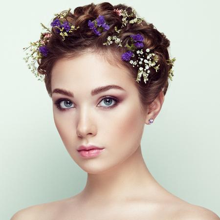 Frente a la hermosa mujer decorado con flores. Maquillaje perfecto. Manera de la belleza. Pestañas. Sombra de ojos cosmética