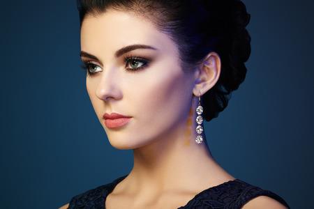 mooie vrouwen: Fashion portret van jonge mooie vrouw met juwelen. Donkerbruin meisje. Perfecte make-up. Schoonheid stijl vrouw met diamant accessoires Stockfoto