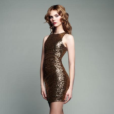 mujer elegante: Retrato de la manera de la mujer elegante con el pelo magnífico. Chica rubia. Maquillaje perfecto. Chica en traje de oro sobre fondo blanco