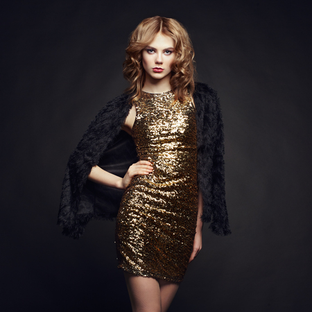 classy woman: Fashion portrait of elegant woman with magnificent hair. Blonde girl. Perfect make-up. Girl in gold dress on black background