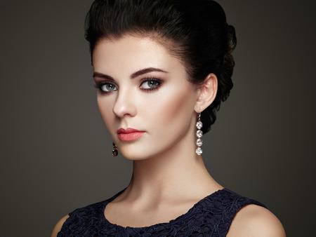 modelos posando: Retrato de la mujer hermosa joven con la joyería. Chica morena. Maquillaje perfecto. Mujer del estilo de la belleza con los accesorios del diamante