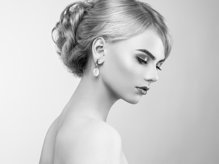 earings: Portrait of beautiful sensual woman with elegant hairstyle.  Perfect makeup. Blonde girl. Fashion photo. Jewelry and dress. Black and white Stock Photo