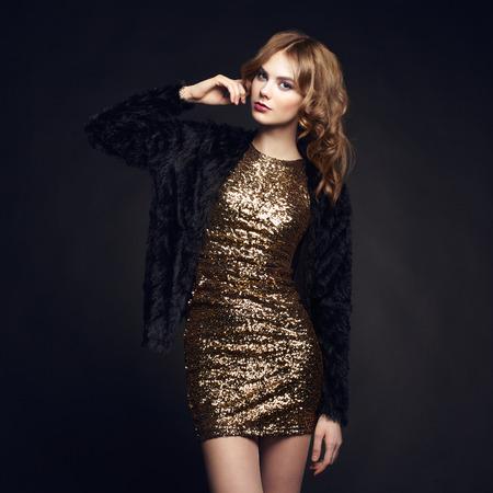 мода: Мода портрет элегантной женщины с пышными волосами. Блондинка. Идеальный макияж. Девушка в платье золото на черном фоне