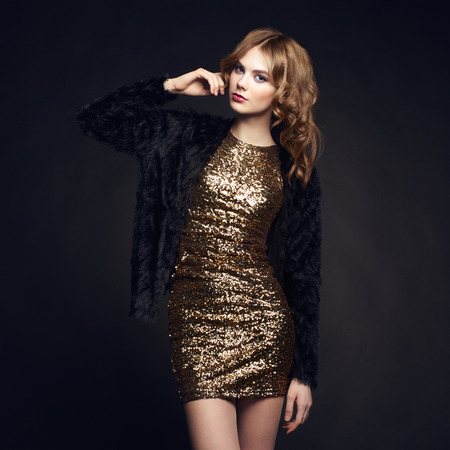 moda: Retrato de la manera de la mujer elegante con el pelo magnífico. Chica rubia. Maquillaje perfecto. Chica en traje de oro sobre fondo negro