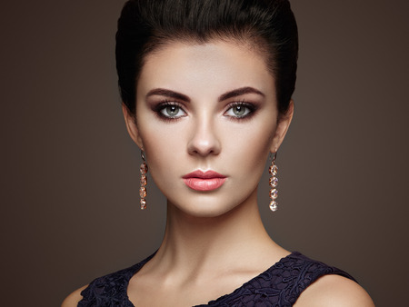 Fashion portrait of young beautiful woman with jewelry. Brunette girl. Perfect make-up.  Beauty style woman with diamond accessories Фото со стока