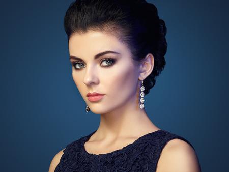 brunette: Retrato de la mujer hermosa joven con la joyería. Chica morena. Maquillaje perfecto. Mujer del estilo de la belleza con los accesorios del diamante