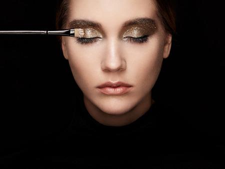 メイクは、アイシャドウを適用されます。美しい女性の顔。完璧なメイク。唇。化粧品アイシャドウ。メイク詳細。アイライナー