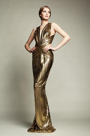 Fashion Portrain van jonge mooie vrouw in gouden kleding. glamour dame brunette met een perfecte make-up en kapsel Stockfoto