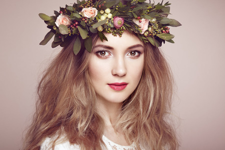 Beautiful blonde woman with flower wreath on her head. Beauty girl with flowers hairstyle. Perfect makeup. Beauty fashion. Spring woman Stok Fotoğraf - 54978339