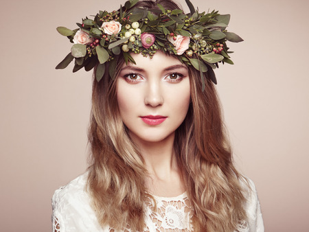 Beautiful blonde woman with flower wreath on her head. Beauty girl with flowers hairstyle. Perfect makeup. Beauty fashion. Spring woman Imagens - 55116775