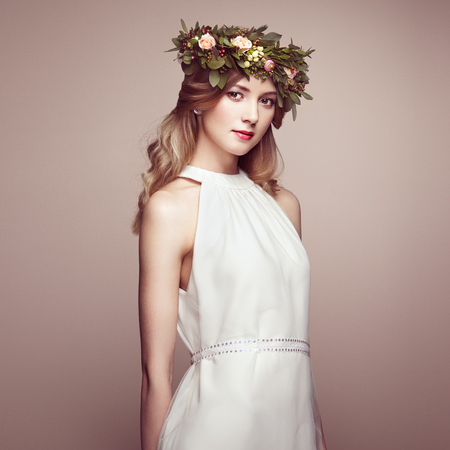 Beautiful blonde woman with flower wreath on her head. Beauty girl with flowers hairstyle. Perfect makeup. Beauty fashion. Spring woman Reklamní fotografie - 55048633