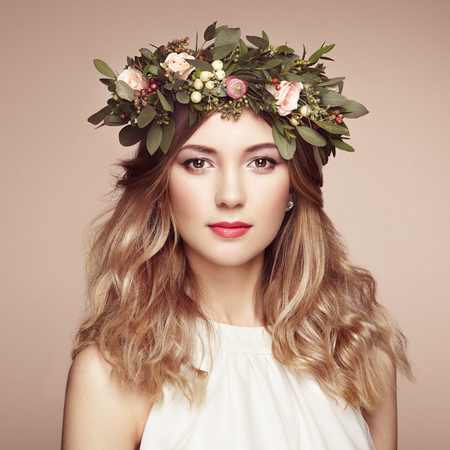 彼女の頭の上の花の花輪と美しい金髪の女性。花の髪型を持つ美少女。完璧なメイク。美容ファッション。女性をはねる