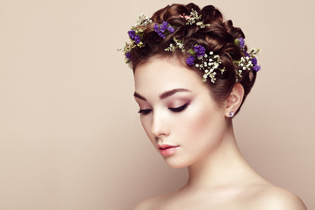 Twarz pięknej kobiety ozdobione kwiatami. Idealny makijaż. Moda Uroda. Rzęsy. Eyeshadow kosmetycznych