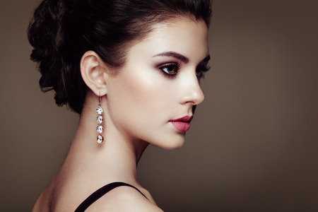 Fashion portrait of young beautiful woman with jewelry. Brunette girl. Perfect make-up.  Beauty style woman with diamond accessories 免版税图像