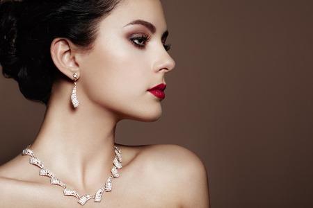 Fashion portret van jonge mooie vrouw met juwelen. Donkerbruin meisje. Perfecte make-up. Schoonheid stijl vrouw met diamant accessoires Stockfoto