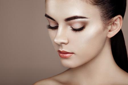 skönhet: Vacker kvinna ansikte. Perfekt makeup. Skönhet mode. Ögonfransar. Kosmetisk ögonskugga. Belysa