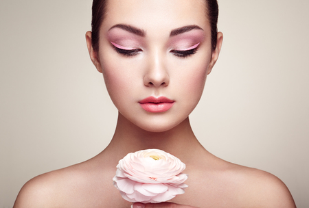 highlight: Portrait of beautiful young woman with flowers. Brunette woman with luxury makeup. Perfect skin. Eyelashes. Cosmetic eyeshadow
