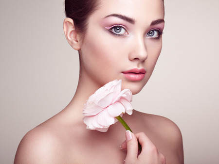 gloss: Portrait of beautiful young woman with flowers. Brunette woman with luxury makeup. Perfect skin. Eyelashes. Cosmetic eyeshadow