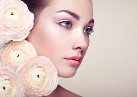 Portrait of beautiful young woman with flowers. Brunette woman with luxury makeup. Perfect skin. Eyelashes. Cosmetic eyeshadow Reklamní fotografie - 56604147