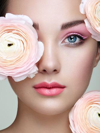 Retrato de mujer joven con flores. Mujer morena con maquillaje de lujo. Piel perfecta. Pestañas. sombra de ojos cosmética Foto de archivo