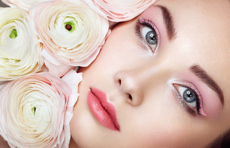 eyeshadow: Portrait of beautiful young woman with flowers. Brunette woman with luxury makeup. Perfect skin. Eyelashes. Cosmetic eyeshadow