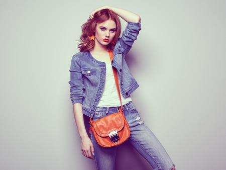 빨간 머리를 가진 아름 다운 젊은 여자의 초상화입니다. 블라우스와 청바지에 소녀. 쥬얼리와 헤어 스타일. 핸드백 소녀