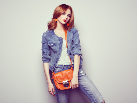 Fashion portrait of beautiful young woman with red hair. Girl in blouse and jeans. Jewelry and hairstyle. Girl with handbag Reklamní fotografie - 57920089
