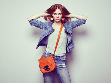 Fashion portret van mooie jonge vrouw met rood haar. Meisje in blouse en spijkerbroek. Juwelen en kapsel. Meisje met handtas Stockfoto