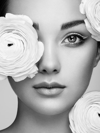 Portrait of beautiful young woman with flowers. Brunette woman with luxury makeup. Perfect skin. Eyelashes. Cosmetic eyeshadow