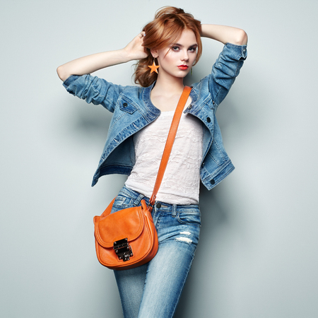 handbag model: Fashion portrait of beautiful young woman with red hair. Girl in blouse and jeans. Jewelry and hairstyle. Girl with handbag