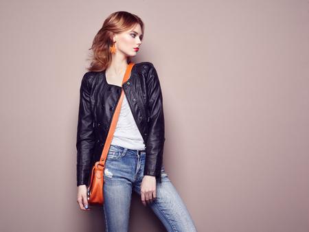 Retrato de la mujer joven hermosa con el pelo rojo. Chica en la blusa y pantalones vaqueros. Joyas y peinado. Muchacha con el bolso